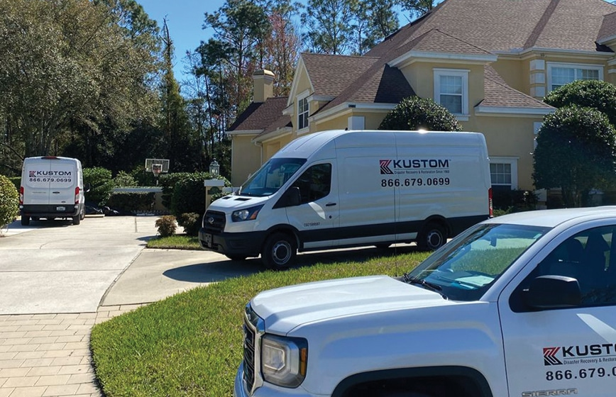 Kustom Disaster Restoration vehicles parked onsite at a residential home for a water damage loss